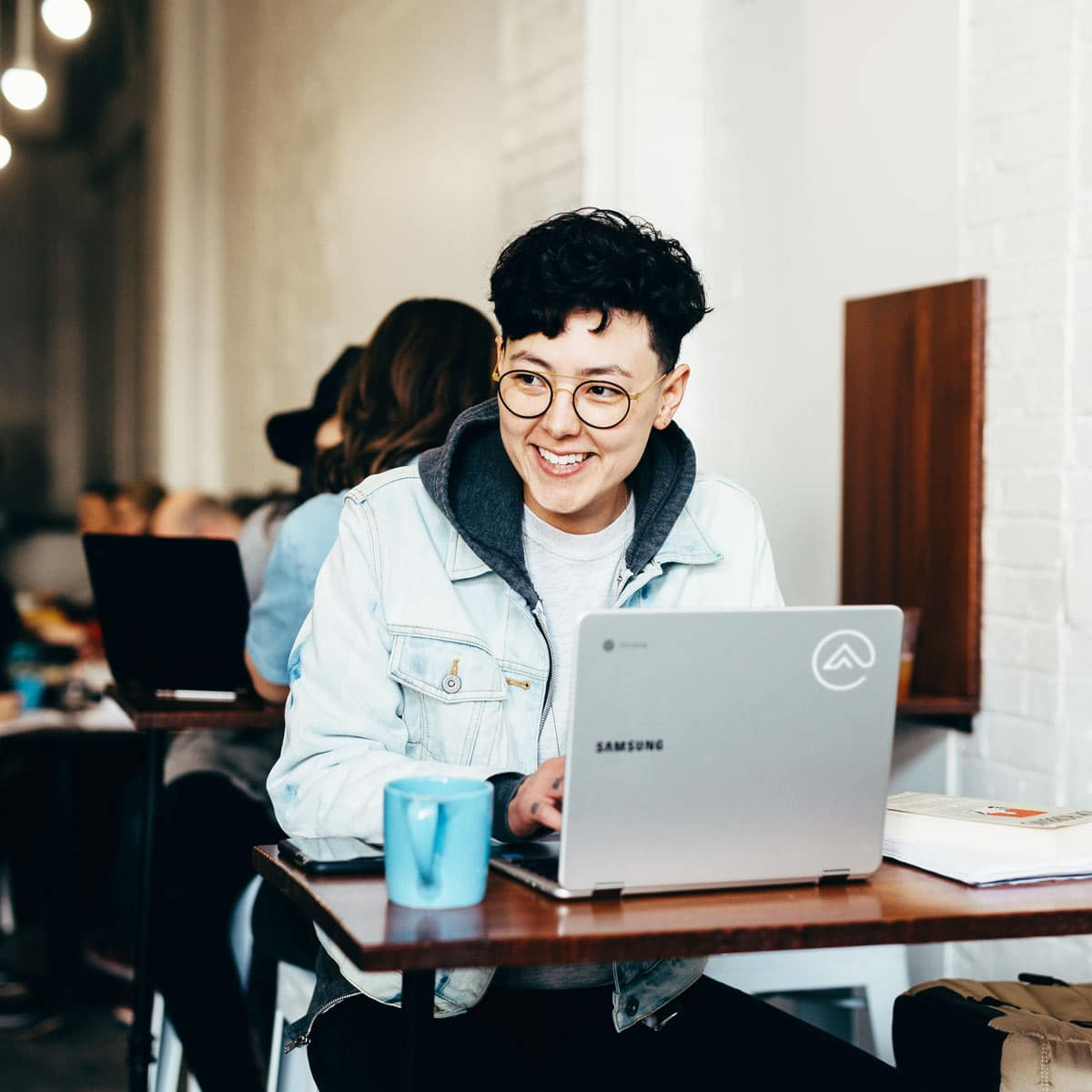 Young man smiling while on a laptop in a coffee shop