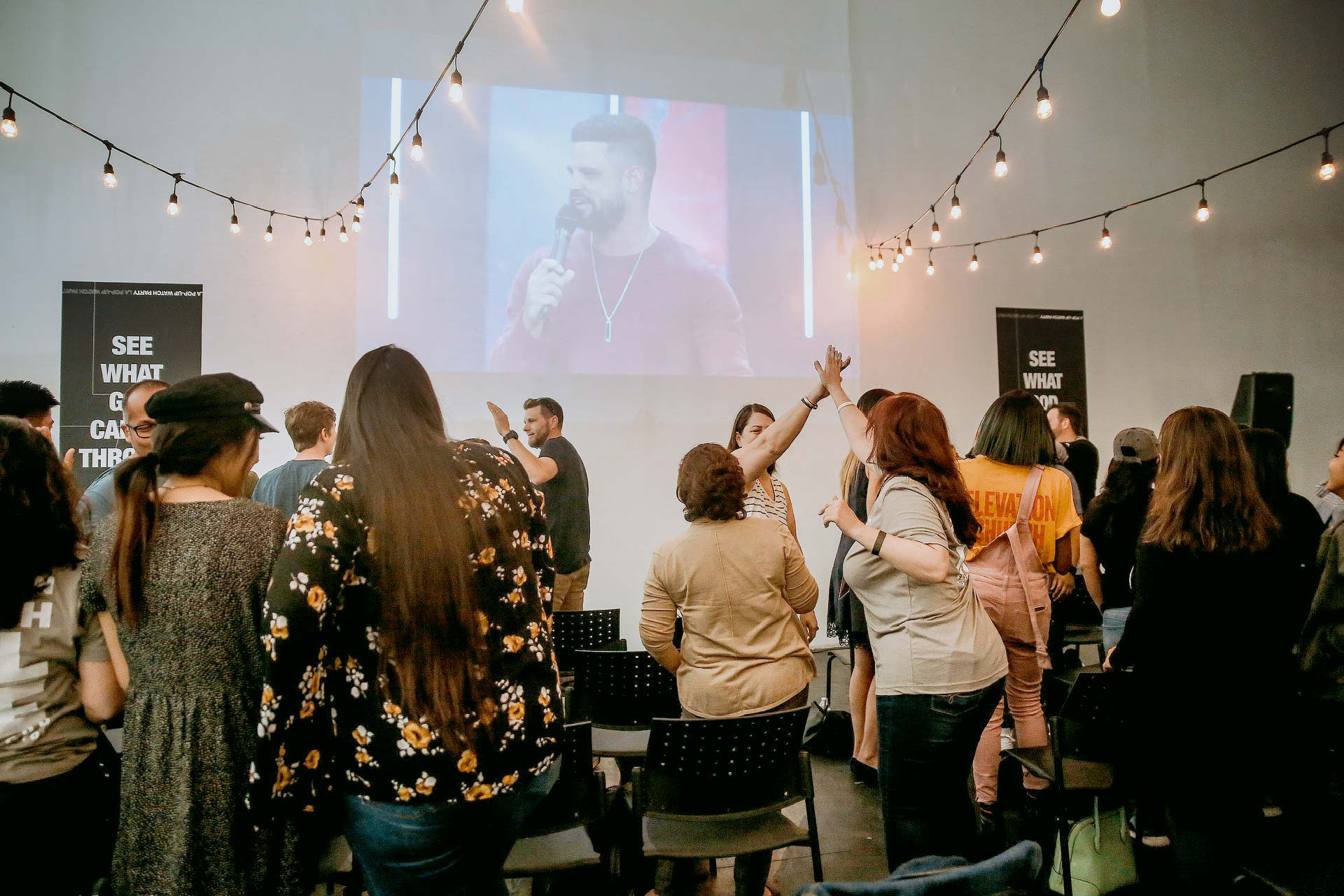 A group of people greeting each other while watching Pastor Steven Furtick at a watch party