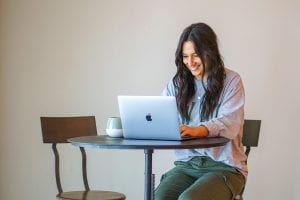 A smiling woman sitting in front of a laptop computer